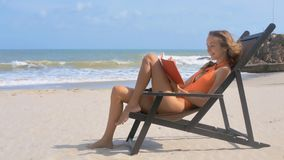 Girl Reads in Chair on Tranquil Ocean Beach Smiles. Smiling girl with hair waved by wind sits and reads red book in chair on tranquil ocean empty beach stock video