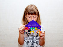 Girl reads greeting card. Teen girl reads blue greating card with cats Stock Photo