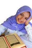 Girl reads the holy Koran. Little muslim girl reads the holy Koran on white background royalty free stock photos