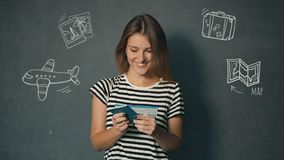 Girl Reads Information on Ticket. Smiling girl in striped t-shirt reading information on ticket, isolated shot in the grey background with travel animation icons stock footage