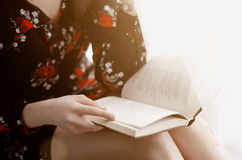 The girl reads an interesting book. The young woman sits at the window and reading a book. out the window the sun is shining Royalty Free Stock Photography