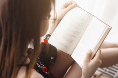 The girl reads an interesting book. The young woman sits at the window and reading a book. out the window the sun is shining Royalty Free Stock Images