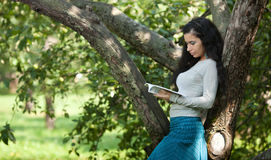 The girl reads near a tree Royalty Free Stock Photography