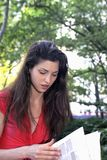 Girl reads newspaper. In park. Photographed June, 2007 in Central Park New York in the USA. She was in her twenties at the time of shoot and is Jewish American stock photo