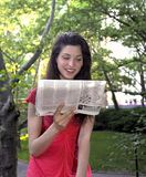 Girl reads newspaper. In park. Photographed June, 2007 in Central Park New York in the USA. She was in her twenties at the time of shoot and is Jewish American royalty free stock photography
