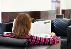 Girl reads the newspaper in an armchair Stock Photography