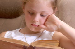 Girl reads old book. Girl lays on floor and reads old book Royalty Free Stock Photography