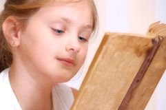 Girl reads old book. Girl lays on floor and reads old book Stock Photo