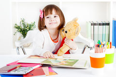 Girl reads a picture book to a teddy bear Stock Photos