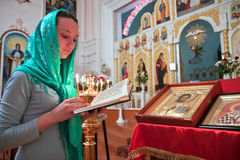 A girl reads a prayer in the church. Girl with a candle reads a prayer in the Orthodox Church Stock Photos