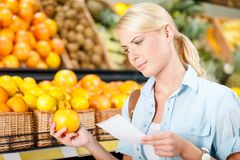 Girl reads shopping list and hands an orange Royalty Free Stock Images