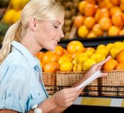Girl reads shopping list near the pile of fruits Royalty Free Stock Image