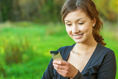 Girl reads sms on mobile phone. Beautiful girl reads message on cellular telephone Royalty Free Stock Images