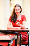 Girl reads sms on phone. Beautiful smiling girl in red dress sits in cafe and reads sms on phone Royalty Free Stock Photography