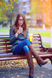 Girl reads sms, rewritten smartphone outdoors in spring or autumn, on the bench, with coffee  tea, breakfast, concep. Girl reads sms, rewritten smartphone Stock Photography
