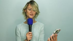 Girl reads text in microphone. From mobile phone stock video