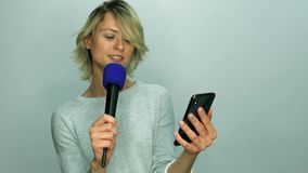 Girl reads text in microphone. From mobile phone stock video footage