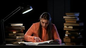 Girl reads and writes information in a notebook. Black background stock video footage