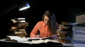 Girl reads and writes information in a notebook. Black background stock footage