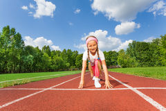 Girl in ready position on bend knee to run Royalty Free Stock Image