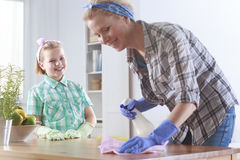 Girl ready to help her mother cleaning Stock Images