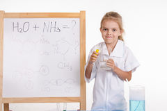 Girl the reagents at blackboard with a formula Stock Photography