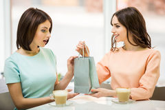 Girl receives the gift. Young beautiful girl sitting in cafe with her friend and receiving a pack with gift royalty free stock photo