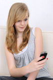 Girl receives a sms. Surprised girl receives a sms and smiles surprised royalty free stock images