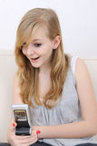 Girl receives a sms and smiles surprised. Blond teenage girl receives a sms and smiles surprised royalty free stock photography