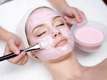 Girl receiving cosmetic pink facial mask Stock Images