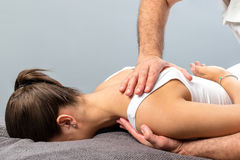 Girl receiving curative osteopathic treatment on shoulder. Close up detail of mail physiotherapist applying pressure on female shoulder blade stock images