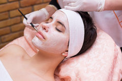 Girl receiving facial mask treatment in beauty spa Stock Photography