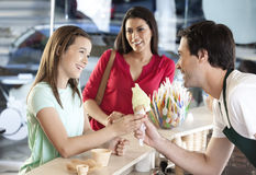 Girl Receiving Ice Cream Cone From Waiter By Mother Stock Photo