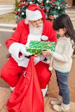 Girl Receiving Present Against Christmas Tree Royalty Free Stock Photos