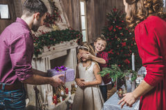 Girl receiving present. Cute little girl receiving Christmas present from her parents stock photo