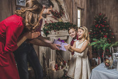 Girl receiving present. Cute little girl receiving Christmas present from her parents royalty free stock photography