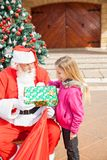 Girl Receiving Present From Santa Claus Royalty Free Stock Photography