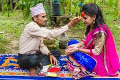 A Girl Receiving Tika and blessings From Her Father at Dashain F. Gorkha,Nepal - Sep 30,2017: A Girl Receiving Tika and blessings From Her Father at Dashain royalty free stock photo