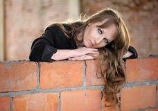 Girl recline on wall Stock Images