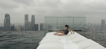 Girl on recliner beside pool. Girl on white recliner beside swimming pool on top of Marina Bay Sands Hotel, Singapore, with cityscape background Stock Image