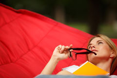 Girl reclining with glasses in hammock Royalty Free Stock Photos