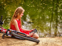 Girl recreation bicycle and watch tablet pc near water. Royalty Free Stock Photography