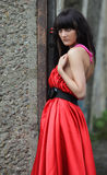 Girl in red. The girl in a red dress on a background of an old concrete wall Royalty Free Stock Photography