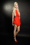 Girl in red. Blonde in a red dress posing in the studio on a black background Royalty Free Stock Photos
