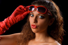 Girl in red. Girl with red lips, red glasses and red gloves on the black background Stock Photos