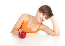Girl with red apple leaning on table Stock Photography