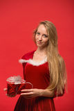 Girl on a red background holds  gift box Royalty Free Stock Photo