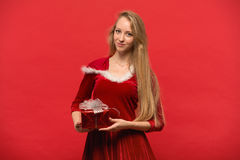 Girl on a red background holds  gift box Royalty Free Stock Photos