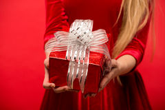 Girl on a red background holds  gift box Stock Photography