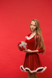 Girl on a red background holds  gift box Royalty Free Stock Photography